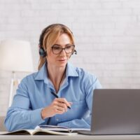 Online consultation with psychologist. Woman with glasses and headphones looks at laptop